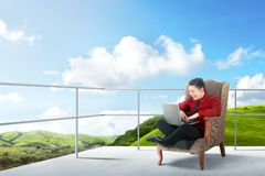 Happy asian businessman sitting on the chair and using laptop on the terrace. With green landscapes view and blue sky background stock photos