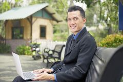 Happy asian businessman sitting and using laptop Royalty Free Stock Image