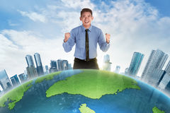 Happy asian businessman standing behind earth planet. With modern building Stock Images