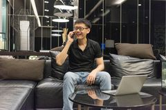 Happy Asian businessman talking on the phone and laptop in living room stock photos