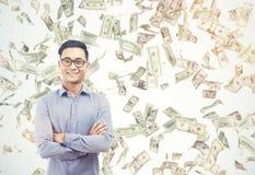 Happy Asian businessman under dollar bill rain on sunny day Stock Image