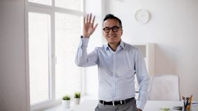 Happy asian businessman waving hand at office stock footage