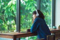 Happy asian casual woman listening music with headphones near wi Stock Image