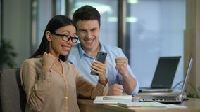 Happy asian caucasian colleagues checking mail on gadget, surprised by good news. Stock footage stock footage
