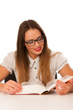 Happy asian caucasian girl lerning in study woth lots of books o Royalty Free Stock Photos