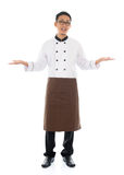Happy Asian chef welcoming pose. Full body Asian male chef hands showing blank space, welcome guest concept, standing isolated white background Stock Image