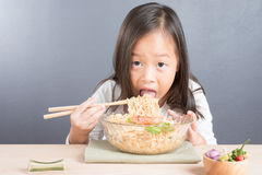Happy Asian child eating delicious noodle. Happy Asian child age 6 years eating delicious noodle, small thai girl eating noodles with chopsticks in glass bowl Stock Images