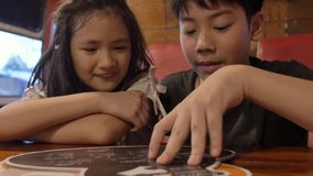 Happy asian child in a cafe or restaurant choose a menu of drinks and food. stock footage