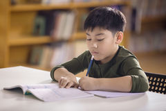 Happy asian child doing homework with smile face. Stock Photo