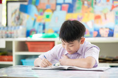 Happy asian child doing homework with smile face. Royalty Free Stock Photography