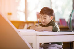 Happy asian child doing homework with smile face. Royalty Free Stock Photos