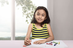 Happy asian child drawing with crayon on white paper. In the home stock photography
