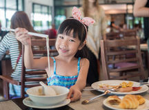 Happy Asian child eating delicious noodle with chopstick Stock Photography