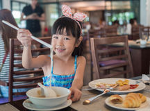 Happy Asian child eating delicious noodle with chopstick Royalty Free Stock Image