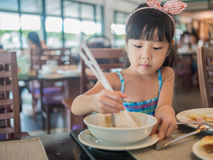 Happy Asian child eating delicious noodle with chopstick Royalty Free Stock Images