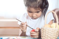 Happy asian child girl drawing and painting on easter egg. Prepare for easter day stock images