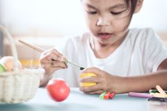 Happy asian child girl drawing and painting on easter egg. Prepare for easter day stock photos