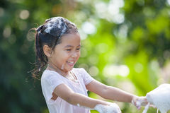 Happy asian child girl having fun to bath and play with foam. In outside Stock Images