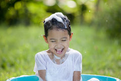 Happy asian child girl having fun to bath and play with foam. In outside Royalty Free Stock Photos
