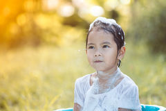 Happy asian child girl having fun to bath and play with foam. In outside Stock Photos