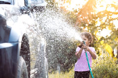 Happy asian child girl help parent washing car Royalty Free Stock Images