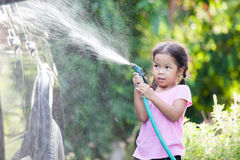 Happy asian child girl help parent washing car on water splash Royalty Free Stock Photos