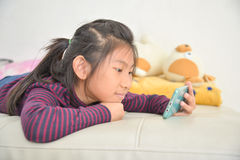 Happy Asian child girl looking at smart phone Stock Photo