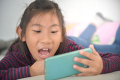 Happy Asian child girl looking at smart phone Royalty Free Stock Images