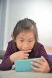 Happy Asian child girl looking at smart phone Royalty Free Stock Photos