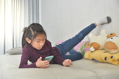 Happy Asian child girl looking at smart phone Stock Photography