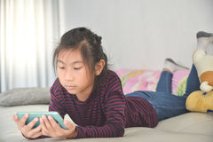 Happy Asian child girl looking at smart phone Royalty Free Stock Photo