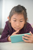Happy Asian child girl looking at smart phone Stock Photos