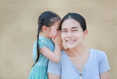 Happy Asian child girl sharing a secret to her mom. Kid girl whispering gossip a something to mother ear.  stock image