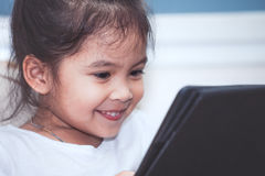 Happy asian child girl sitting on sofa smiling Royalty Free Stock Photography