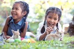 Happy asian child girls playing with little bunny rabbit with love and tenderness in the garden. At easter egg hunt royalty free stock photography
