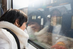 Happy asian child looking out train window outside Stock Images