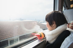 Happy asian child looking out train window outside Stock Photography
