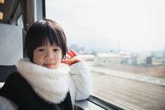 Happy asian child looking out train window outside Royalty Free Stock Photography