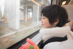 Happy asian child looking out train window outside Stock Photo