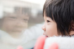 Happy asian child looking out train window outside Royalty Free Stock Images