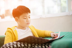Happy asian child reading book with smile face. Royalty Free Stock Photos