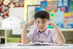 Happy asian child reading book and thinking about that royalty free stock photos