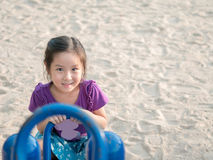 Happy Asian child on a seesaw Royalty Free Stock Photos