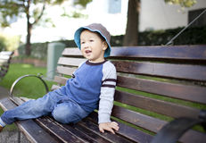 Happy asian child sitting on  the garden chair Stock Image