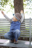 Happy asian child sitting on  the garden chair Royalty Free Stock Photos