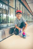 Happy asian child sitting and tying to tie shoelaces near walkwa. Happy asian child sitting and tying to tie shoelaces near electric speedwalk in modern airport Stock Photo