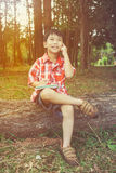 Happy asian child smiling on wooden log in national park. Outdoo. Happy asian boy can resolve problem at park. Outdoors in the day time with bright sunlight Royalty Free Stock Images