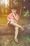 Happy asian child smiling on wooden log in national park. Outdoo. Happy asian boy can resolve problem at park. Outdoors in the day time with bright sunlight Stock Images
