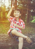 Happy asian child smiling on wooden log in national park. Outdoo. Happy asian boy can resolve problem at park. Outdoors in the day time with bright sunlight Stock Image