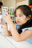 Happy Asian child  touching with smart phone Royalty Free Stock Photos